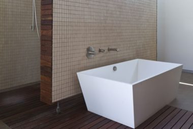 contemporary-bathroom-with-wooden-flooring-white-geometric-bath-tub